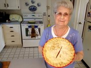 Aliene Bieber, Lawrence, displays a homemade cherry pie while an apple pie cools on the stove behind her. Bieber is a long-time participant in the Douglas County Fair open baking contest, where her pies have won champion and reserve champion ribbons for years.