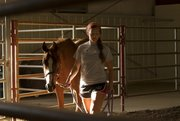Andrea Steward, 16, of Lawrence, leads her horse around the arena Saturday in the Community Building at the Douglas County Fairgrounds. Andrea said she was getting the horse used to the arena before the show began.