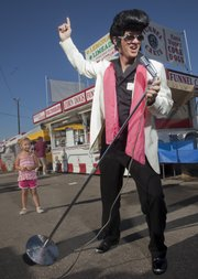 Wade Morrow, who will be participating in the first Elvis Spectacular on Saturday in downtown Lawrence, was at the Douglas County Fair Thursday in full Elvis mode to promote the event. Morrow is also a square-dance caller and was at the fair for a performance with the Happy Time Squares square-dance organization.