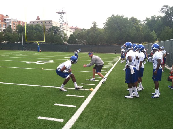 KU assistant Clint Bowen runs sophomore Victor Simmons through a defensive backs drill at Friday's practice.