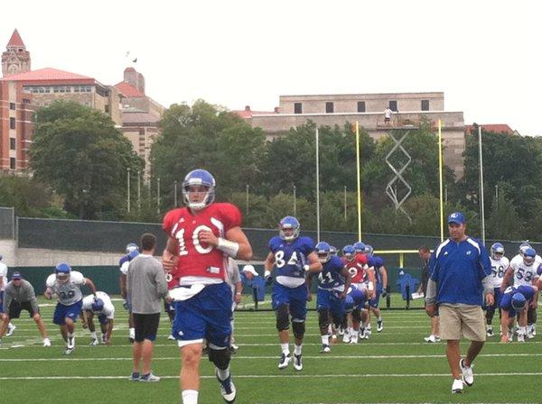 KU quarterback Dayne Crist (10) leads the Jayhawks through warm-ups at Saturday's practice.