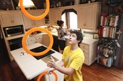 Noah Schmeissner, a 15-year-old juggler, practices his talent with a set of rings as his mother Baretta Schmeissner works in the kitchen of their Valley Falls home on Wednesday, Aug. 1, 2012. Schmeissner, who competes in national juggling competitions yet has only been actively juggling for two years, says that he practices sometimes up to three hours a day in their kitchen.