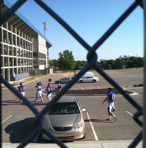 The KU kickers and specialists head from warm-ups at the practice fields to Memorial Stadium for their day's work.