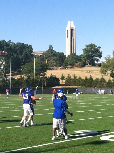 Running backs coach Reggie Mitchell and the KU ball carriers work on ball security during Tuesday's practice.