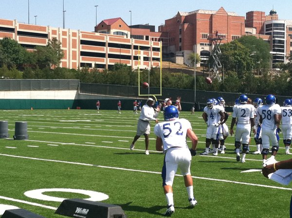 KU linebackers coach zips a pass toward freshman Dom Bickus during an interception drill.