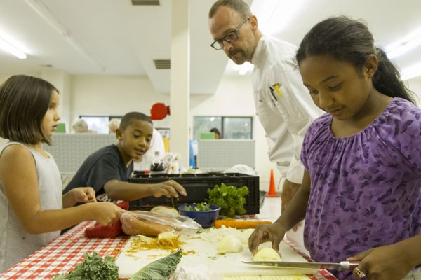 Lawrence chef Rick Martin checks in on, from left, Elle Martin, 7, Lawrence, Kailani Espinales, 9, Baldwin City, and his sister Skylynn Espinales, 11, as they prepare vegetables during a three-hour cooking clinic held at the Just Food warehouse, 1000 E. 11th St., Wednesday, Aug.  8, 2012. The clinic taught those in attendance how to make red beans and rice and pico de gallo.