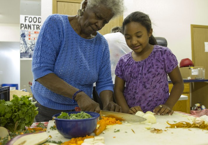 Skylynn Espinales, 11, Baldwin City, watches her grandmother, Mildred Reed, chop carrots during a three-hour cooking clinic held Wednesday, Aug. 8, 2012, at the Just Food warehouse, 1000 E. 11th St.. The clinic taught those in attendance how to wash, chop and measure food along with creating a nutritious dish of red beans and rice with pico de gallo.