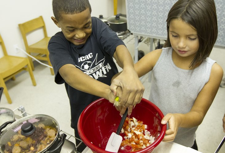 Kailani Espinales, 9, Baldwin City, left, squeezes a lime with all his might as Elle Martin, 7, Lawrence, stirs the bowl as the two make pico de gallo during a cooking class at the Just Food warehouse, 1000 E. 11th St.