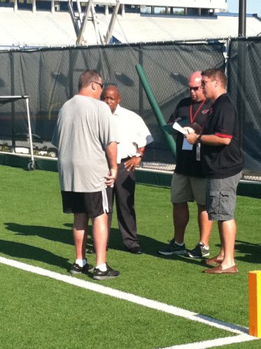 KU coach Charlie Weis huddles with a few scouts from the NFL's Arizona Cardinals before the beginning of Thursday's practice. The presence of NFL scouts has been a regular thing at every KU practice so far this season.