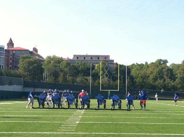 Several members of the KU offensive line push the sled during Thursday morning warm-ups prior to the start of practice.