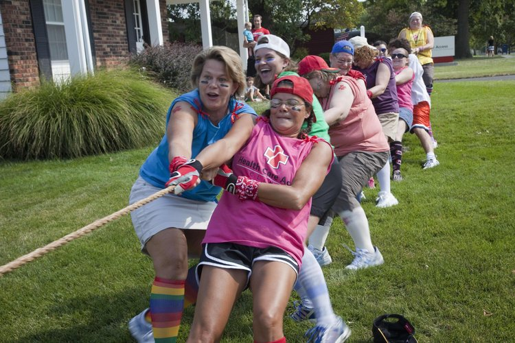 Health Care Access staff members Brenda Waite, left, and Kim Johnson participate in the tug-of-war contest that the clinic had with it neighbor Douglas County Dental Clinic on Thursday to raise awareness about Kansas Primary Health Safety Net Clinic Week.