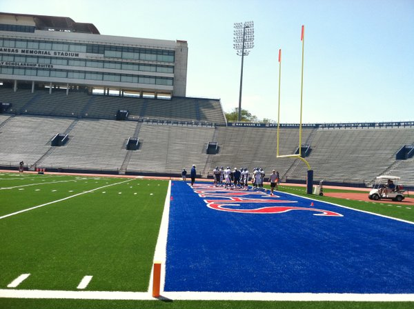 KU's defensive line works in the north end zone on the far side of the field during Friday's practice.