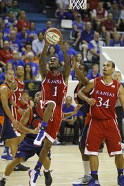 Naadir Tharpe (1) drives as teammate Perry Ellis, right, looks on during an exhibition between Kansas and AMW Team France on Saturday, Aug. 11, 2012, at the Coubertin Stadium in Paris.