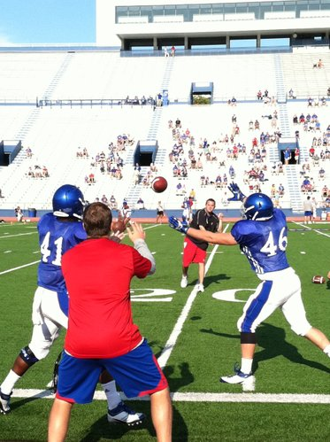 KU tight ends coach Jeff Blasko watches tight ends Jimmay Mundine (41) and Adam Novak (46) work the distraction drill.