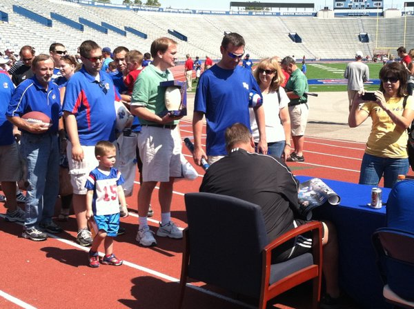 KU fans line up to get autographs from KU football coach Charlie Weis, who posed for pictures, cracked jokes and signed all kinds of memorabilia.