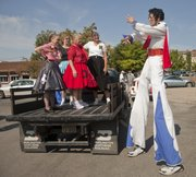 Richard Renner, right, strikes a pose for members of the Happy Time Squares square-dance organization before the first Downtown Lawrence Elvis Spectacular kicks off with a parade Saturday. The parade was followed with an Elvis Sing-Off competition and the annual Rev It Up car show in South Park.
