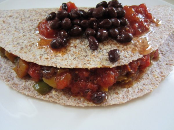 Fajita veggies with black beans, chopped mango and peach salsa on a sprouted tortilla.