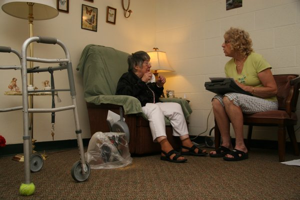 Mary Barker, a case manager with the Jayhawk Area Agency on Aging, reassesses the needs of Vivian Glessner, a 91-year-old resident at Briarcliff Care Center in Topeka. Barker meets with Glessner every 11 months to make sure she's receiving the appropriate level of Medicaid-funded services. An association representing the state's area agencies on aging has bid on a contract that would have case managers for the frail elderly also assess the needs of people who are physically disabled or have traumatic brain injuries.