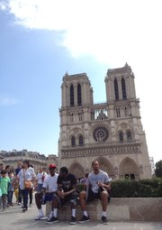 Kansas players Rio Adams, Milt Doyle and Travis Releford sit in front of the Notre Dame Cathedral on Sunday, Aug. 12, 2012, in Paris.