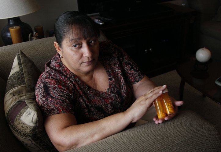 In a Thursday, July 26, 2012 photo, Sandra Pico, 52, holds medications she takes, at her home in North Miami Beach, Fla. Pico makes about $15,000 a year working about 20 hours a week as a home health aide, a bit too much to qualify for Medicaid, but not enough that she can afford private insurance. She thought she'd be getting health insurance after the Supreme Court upheld the health care law. Then she learned her own governor won't agree to expand Medicaid under the law which would have given her coverage.