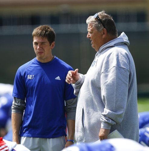 Kansas head coach Charlie Weis talks with his son Charlie Weis Jr. during practice on Tuesday, Aug. 14, 2012.
