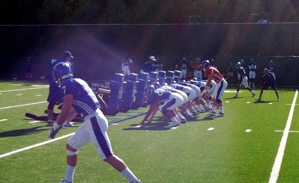 KU's first-string offense simulates a snap against the sled during Wednesday's morning practice.