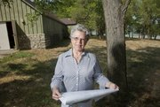 Martha Parker, director of the Wakarusa River Valley Heritage Museum, holds blueprints for the museum expansion project that will break ground this fall. The museum, pictured at left in background, features much of the history of the Wakarusa Valley and the communities that were affected by the construction of Clinton Lake, pictured in background at right near Bloomington Beach. Also planned at the site on Sept. 8 will be a Sigel Harvest Home Picnic Dinner and Music Festival. This festival was the precedent for the annual Douglas County Fair.
