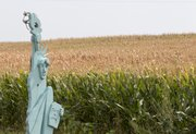 In this Aug. 1, 2012 photo, a rendition of Lady Liberty stands in front of a parched corn field near Crete, Neb. The front row of corn remains green because it is irrigated by a lawn sprinkler. The latest U.S. drought map shows that excessively dry conditions continue to worsen in the Midwest states that are key producers of corn and soybeans. This is the worst U.S. drought in decades. The weekly U.S. Drought Monitor map released Thursday, Aug. 9. 2012 shows that the area gripped by extreme or exceptional drought rose nearly 2 percent to 24.14 percent.