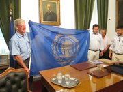 Lawrence Mayor Bob Schumm, left, receives the official flag of the Municipality of Messolonghi, Greece, from Mayor Panagioeis Kaesoulis, holding flag at right. With them are other members of the Sister City delegation to Iniades, Greece. Messolonghi is responsible for the administration of the area of Iniades.