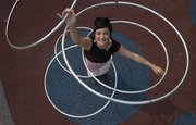 Hula-Hoop dancer Luna Breeze (real name Brie Blakeman) shows off a five-hoop trick Thursday on a playground at Loose Park in Kansas City, Mo. Breeze is among area performers bringing their acts to Lawrence's Busker Festival, which begins Friday.