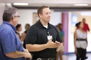 School resource officer Mike Cobb, right, watches over the cafeteria Friday at Lawrence High School. This year, the Lawrence Police Department has reduced its number of school resource officers from six to four to increase the number of patrol officers.