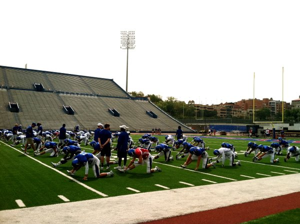The KU football team runs through pre-game stretches just as it would on Saturdays this fall. The season opener is now just two weeks away. 