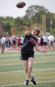 During a quarterback drill at the annual Lawrence High School Mom's Camp, Angie Sutter, mother of Lions junior Tucker Sutter, throws to a receiver with the Lions football team Saturday, Aug. 18, 2012. The moms, and at least one grandmother, ran drills and sprints with their Lion kin.