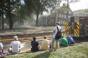 Members at the Sigma Chi fraternity, 1439 Tenn., watch smoke billow from the roof area of their house on Wednesday, Aug. 22, 2012 .