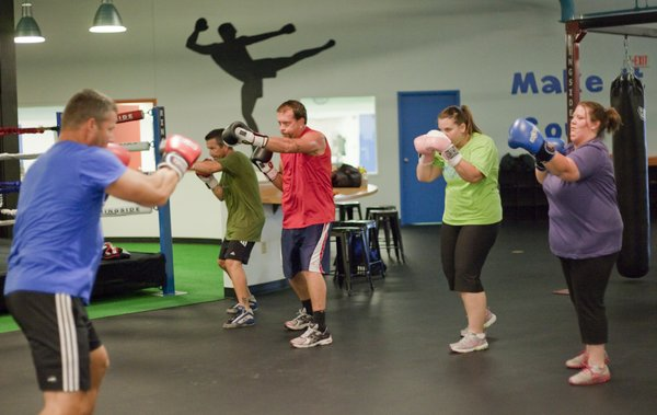 At left boxing instructor John Heleniak, leads a group through a class at Punch Boxing and Fitness, 4931 W. 6th St. Participating in the class from left are Heleniak, Mike McAtee, Craig Eddis, Caitlin Brown and Ali Cook.