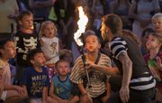 Kids help Jason Divad, Kansas City, Mo., blow out a flame that he used in his performance during the annual Buskerfest held in downtown Lawrence, Friday, August 24, 2012. The performances continue tomorrow.