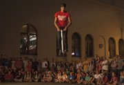 Mike Hughes of the Pogo Dudes bounces above the crowd during the annual Buskerfest held in downtown Lawrence Friday, August 24, 2012. The performances continue tomorrow.