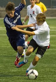 Lawrence High's Nick Andrews, right, and Manhattan's Jacob Stutheit (3) battle for control of the ball during their soccer match Friday, August 24, 2012, at LHS.