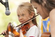 Seven-year-old Isabella Ball, Lawrence, performs with her music teacher Tricia Spencer.