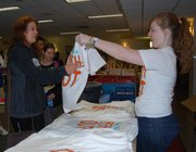 Junior Jordan Key hands junior Sam Tinsdeall a free T-shirt Saturday in the Kansas Union during the Center for Community Outreach's Super Service Saturday. Volunteers received a free T-shirt and pizza after registering to volunteer.