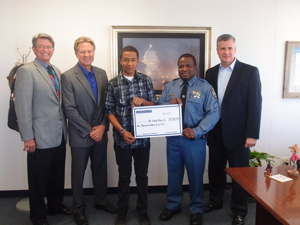 A Valor Public Safety Award Scholarship is presented to Clark Rials Jr., center, whose father Sgt. Clark Rials of the Douglas County Sheriff's Office, second from right, was a 2011 Valor Awards honoree. Presenting the scholarship are, from left, John Ross, chairman of the Lawrence Chamber board of directors; Harry Herington, CEO of NIC Inc., the signature sponsor and co-founder of the Valor Public Safety Awards Program; and Greg Williams, president and CEO of the Lawrence Chamber of Commerce. The Valor Awards honor the community's first responders and the commitment of their families.