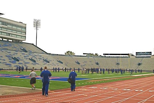 SDSU coach John Stiegelmeier (with bag) walks onto the Memorial Stadium turf to address his team prior to Friday's walk-through.