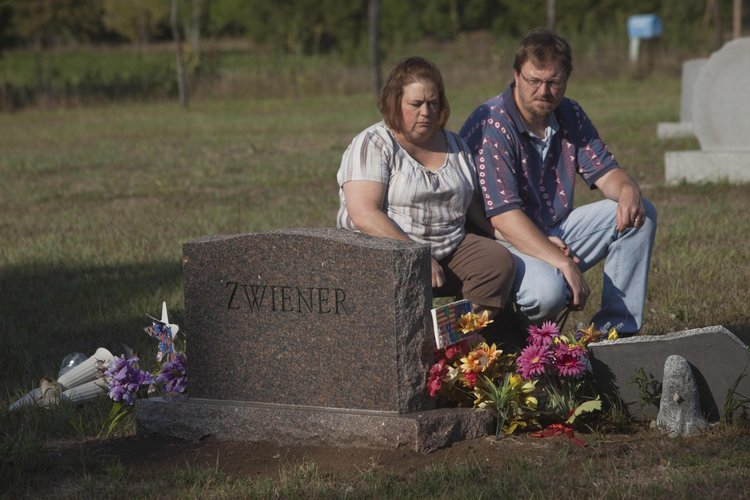 Lisa Zwiener and her husband, Raymond Zwiener, sit on a bench next to their son's gravesite in Rock Creek cemetery, west of Clinton Lake, on Thursday, Aug. 30, 2012.