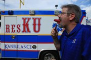 Kanbulance tailgater Wes Smith takes a bite of a spicy dog at the Kansas University football team's 2012 home opener against South Dakota State University.
