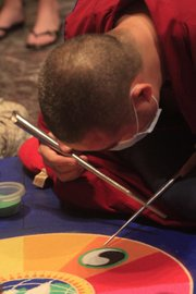 "Seven Buddhist monks will be at the Spencer Museum of Art this week painstakingly constructing a sand painting called dul-tson-kyil-khor, meaning ""mandala of colored powder."" On Friday, the monks will toss the sand painting into Potter's Lake in a symbolic gesture."