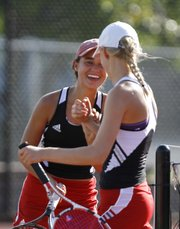 Lawrence High doubles partners Brooke Braman, left, and Lilly Abromeit have a laugh during a break between matches on Tuesday, Sept. 4, 2012 at LHS.