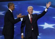 Former President Bill Clinton waves after addressing the Democratic National Convention as President Barack Obama greets in Charlotte, N.C., on Wednesday.