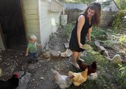 Meryl Carver-Allmond waits for her 1-year-old son Knox to catch up as the two go to feed the chickens on Sept. 6 in the backyard of their East Lawrence home.