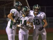 Free State's Sam Hearnen (83), Tye Hughes (14), and Zach Bickling (82) celebrate Hughes' punt return for a touchdown to end the first half during Free State's game against Shawnee Mission West Friday, Sept. 07, 2012, in Overland Park.