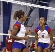 Kansas University players Tiana Dockery, left, and Tayler Tolefree celebrate Dockery's block, which earned the Jayhawks a point during the second of two sets against College of Charleston, Friday, Sept. 7, 2012 at the Horejsi Center.